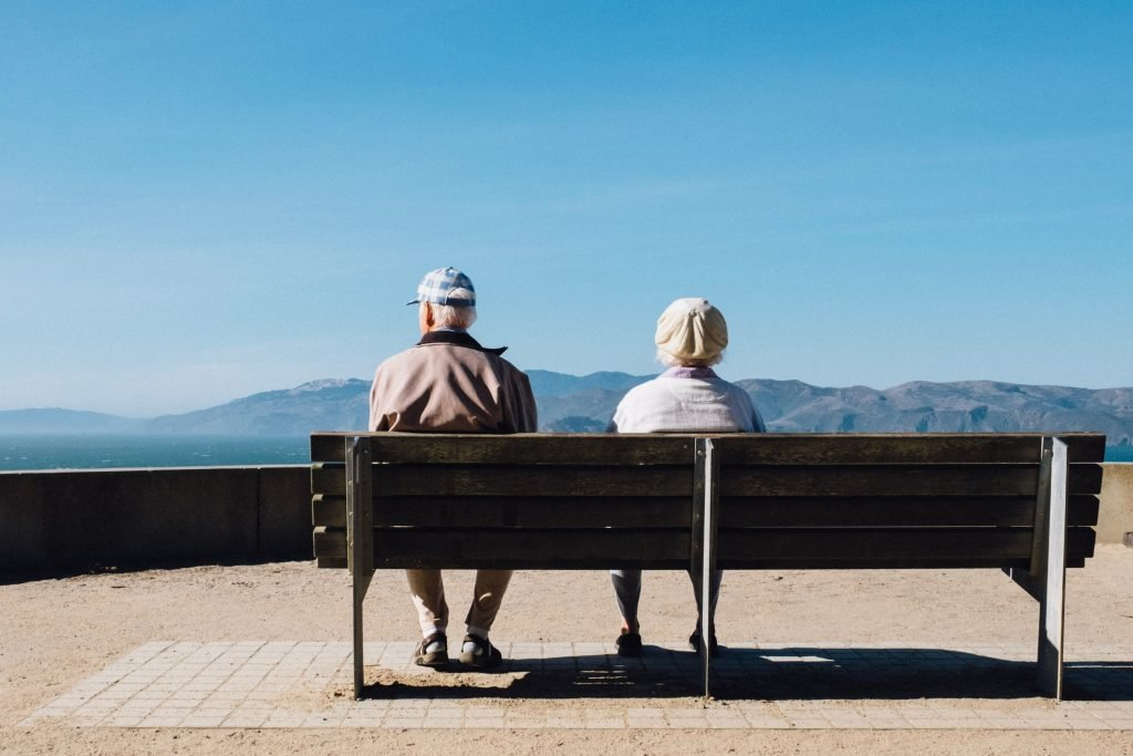 man and woman sitting on bench facing sea retirement