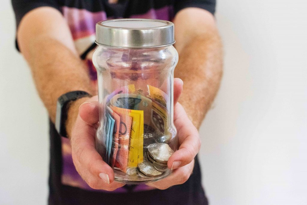 person holding clear glass jar filled with money