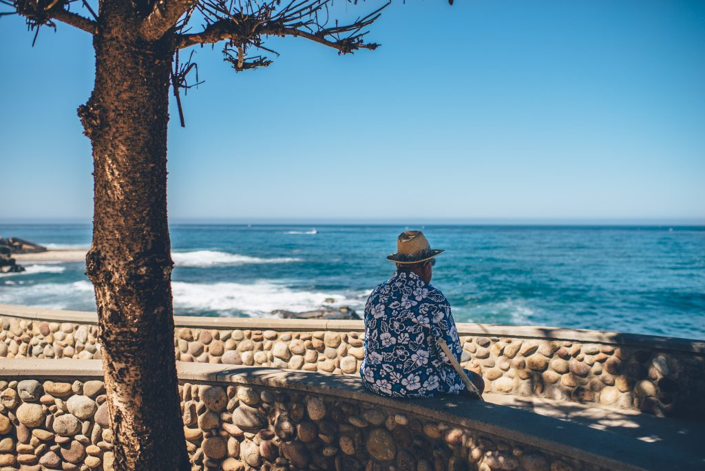 retire man sitting facing sea